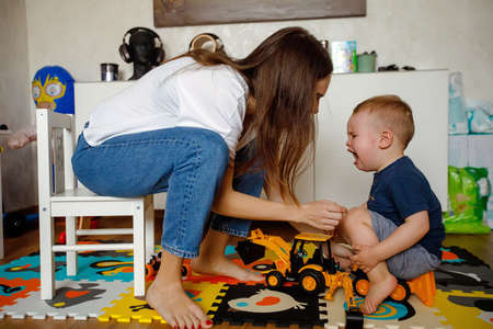 Side view of young mother sitting on child chair and soothing crying baby while playing with cars in children room at home Stok Fotoğraf