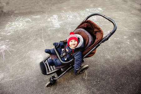 Top view on little smiling child dressed in warm overalls sitting in pram and looking at camera in courtyard