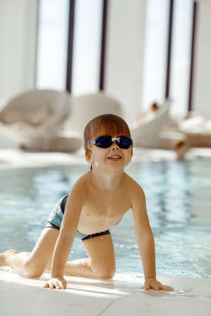 Happy wet child in swimming glasses standing on knees by pool after swimming