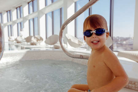 Happy wet child in swimming glasses standing on knees by pool after swimming looking at camera