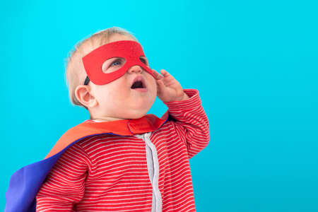 Cute baby in superhero mask and cape looking away against blue background