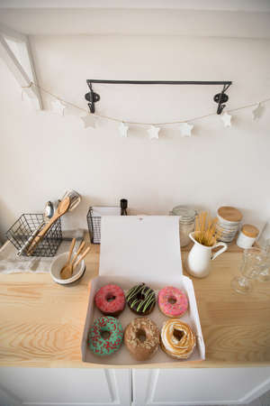 From above shot of open box with delicious fresh donuts lying on wooden tabletop in kitchen