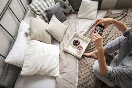 From above shot of woman sitting on bed and taking picture of tea and doughnut on tray with smartphone Stock fotó