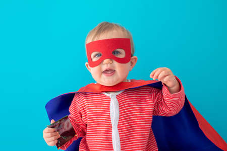 Back view of cute baby in superhero mask and cape looking at camera blue background