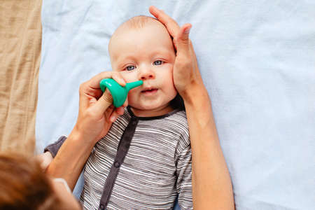 From above woman using nasal aspirator and tenderly holding head of little kid lying on bed