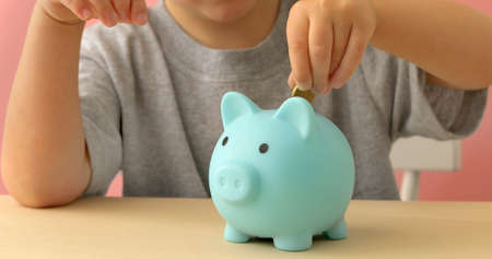 Little boy puts coins and shakes piggy bank at home 스톡 콘텐츠
