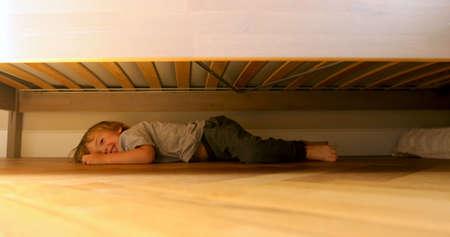 Das versteckte Baby liegt lachend und krabbelt unter dem Bett hervor. Kind sucht etwas unter dem Bett.