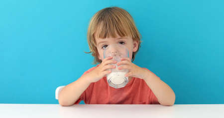 Little cute boy is drinking milk from a glass on blue background