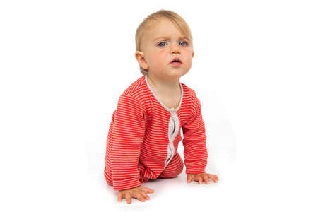 Adorable blue eyed baby with in red romper crawling on all fours and looking at camera in surprise on white background