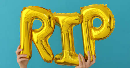Golden RIP words made of inflatable balloons on blue background