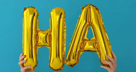 Golden HA word made of inflatable balloons on blue background Imagens