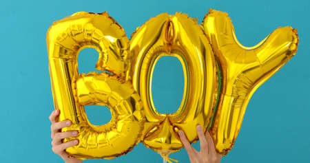 Golden BOY words made of inflatable balloons on blue background Imagens
