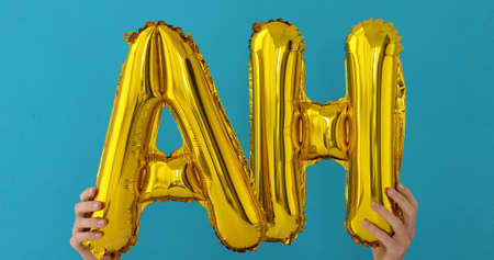 Golden AH word made of inflatable balloons on blue background