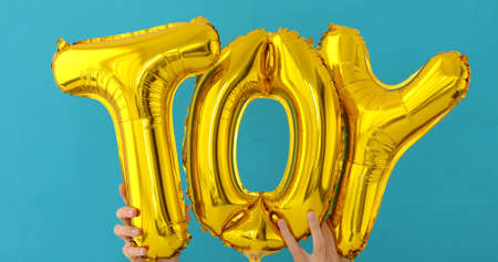 Golden TOY words made of inflatable balloons on blue background Imagens