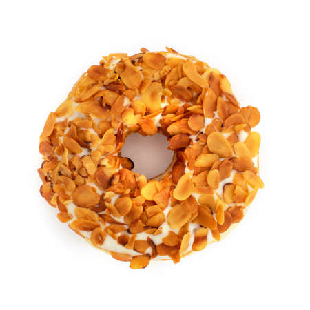 From above tasty aromatic doughnut with white glaze and peeled nuts on top