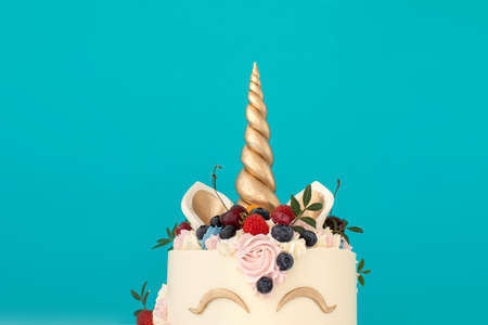 Unicorn cake with copy space to side on blue background
