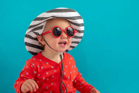 Little Girl in sunglasses wearing hat isolated on blue background