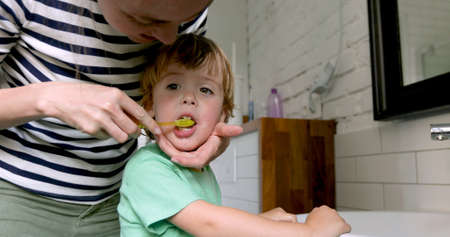 Mother teaching and helping child son how to brush his teeth