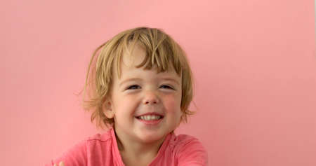 Cute merry light haired kid in bright t-shirt laughing at camera on pink background