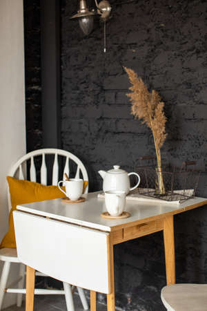 Folding table with cups and white tea pot and chair with pillow against black brick wall in kitchen