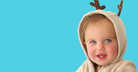 Cute little baby girl smiles in a deer costume on blue background Stock fotó