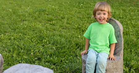 Cheerful kid laughing while sitting on stone chair on green meadow in summer park Reklamní fotografie