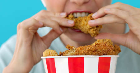 Girl eating chicken wings, high calorie food and health risks, cholesterol blue background Stock Photo