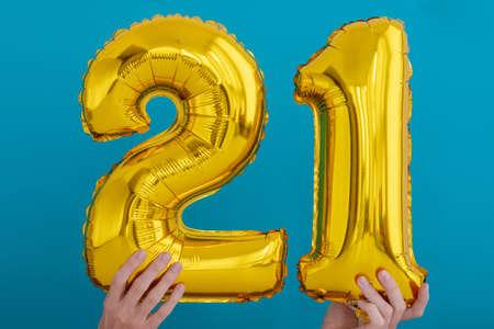 Gold foil number 21 twenty one celebration balloon on a blue background