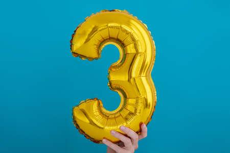 Gold foil number 3 three celebration balloon on blue background Archivio Fotografico