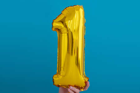 Gold foil number 1 one celebration balloon on blue background
