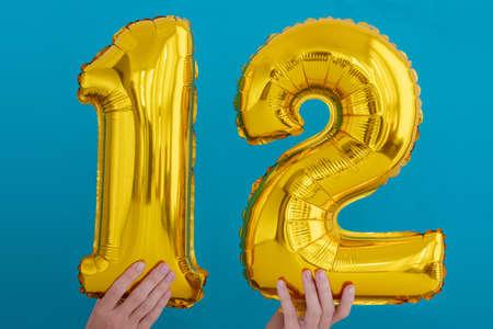 Gold foil number 12 twelve celebration balloon on a blue background