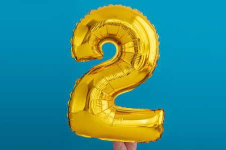 Gold foil number 2 celebration balloon on a blue background