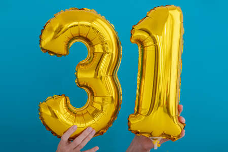 Gold foil number 31 thirty one celebration balloon on a blue background