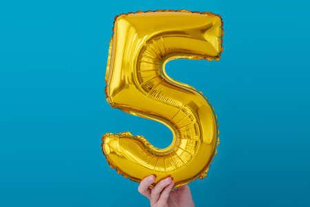 Gold foil number 5 celebration balloon on blue background