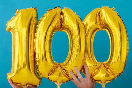 Gold foil number 100 one hundred celebration balloon on a blue background Stock Photo