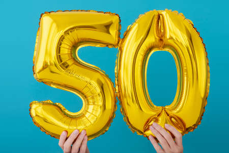 Gold foil number 50 fifty celebration balloon on a blue background Stock Photo