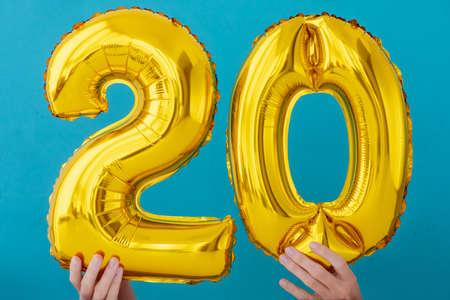 Gold foil number 20 twenty 0 celebration balloon on a blue background