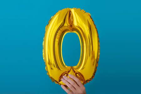Gold foil number o 0 zero celebration balloon on blue background Stock Photo