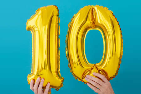 Gold foil number 10 ten celebration balloon on a blue background Stock Photo