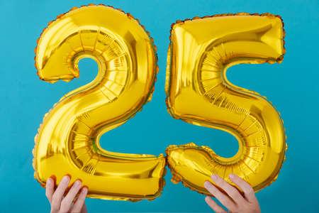 Gold foil number 25 twenty five celebration balloon on a blue background