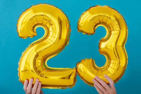 Gold foil number 23 twenty three celebration balloon on blue background Stock Photo