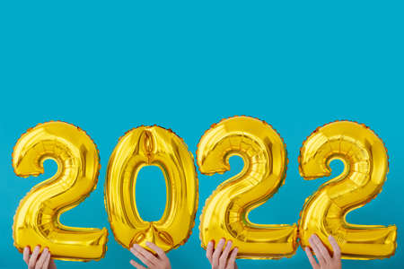 Gold foil number two thousand and twenty two 2022 celebration balloon on blue background Stock Photo
