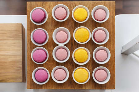 Top view of colourful macaroons served in cups arranged in even square shape on wooden stand Stock Photo