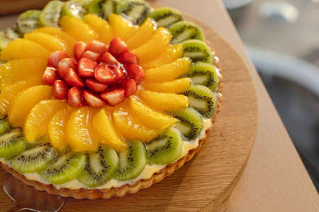 Tempting shortcrust pastry with cream and fresh sugary fruits and berries served on wooden tray