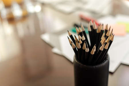 From above bunch of graphite pencil in holder on table with blurred stationery items