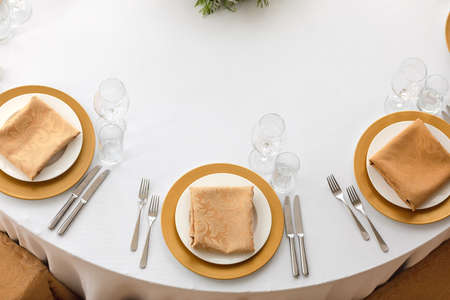 Top view of elegant plates with folded napkins and glassware served on clean white cloth in restaurant Stockfoto