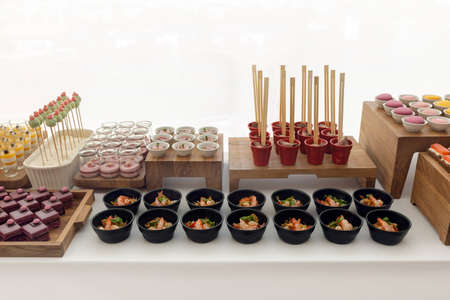 Assorted delicious sweets and pastry served on wooden trays at restaurant buffet isolated on white background Stockfoto