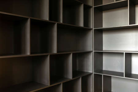 Variously shaped empty shelves of wooden cabinet ready for content in corner 스톡 콘텐츠