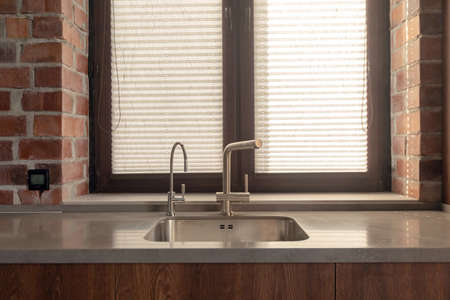 Stainless kitchen sink with modern faucets against window with shutters in red brick wall
