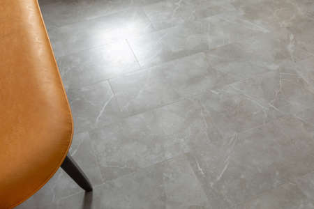 Top view of leather chair over floor made of gray marble tiles reflecting daylight Zdjęcie Seryjne